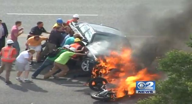 Bystanders Lift A Burning Car To Save Trapped Motorcyclist