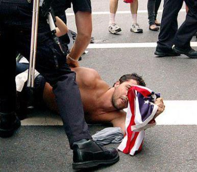Man holding US flag while being held to ground by police