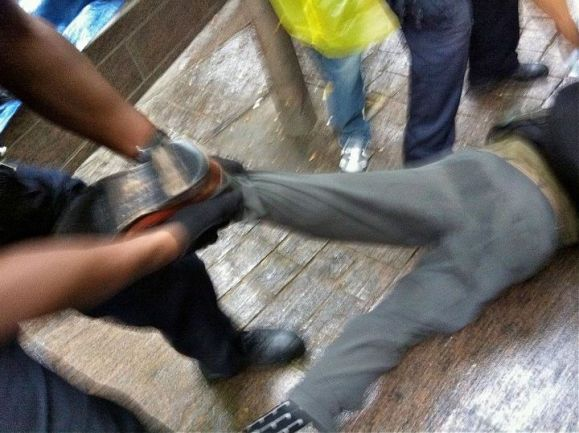 Occupy Wall Street man on ground being arrested being dragged by his leg