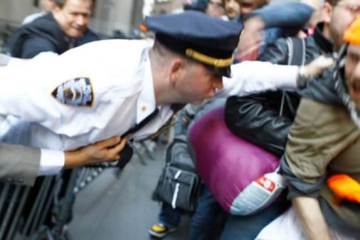 Occupy Wall Street police officer reaching accross barrier to grab protester