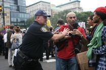 Police officer shoving back man with camera