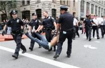 Police officers carrying protestor by legs and arms