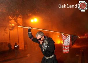 Occupy Oakland fire and gas in background man running with flag