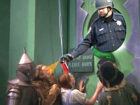 pepper spraying cop John Pike spraying Dorothy Lion Scarecrow Tinman in Wizard of Oz