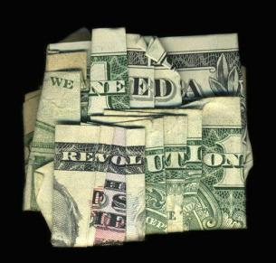Folded dollar bills to read we need a revolution