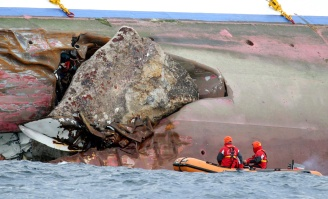 Firefighters on a dinghy examine a large rock emerging from the side of the luxury cruise ship Costa Concordia, the day after it ran aground on Sunday, January 15, 2012. (AP Photo/Andrea Sinibaldi, Lapresse)