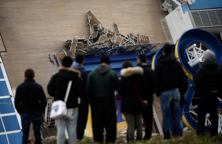 People look at the deck chairs piled on the deck of the leaning Costa Concordia, on January 15, 2012, after the cruise ship ran aground on January 13. (Filippo Monteforte/AFP/Getty Images)