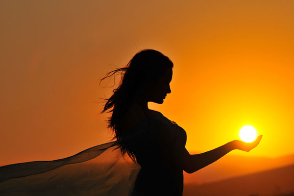 woman holding the sun in the palm of her hand
