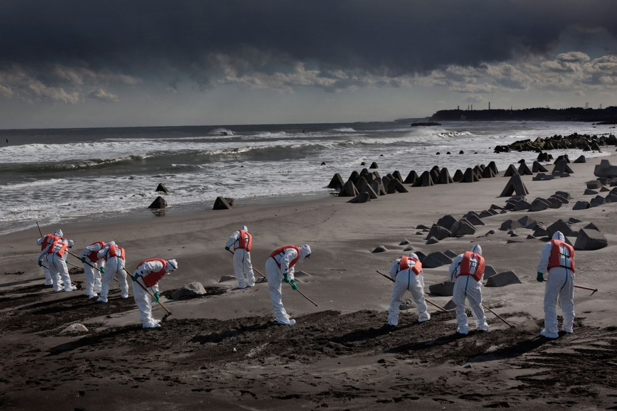 Feb. 27, 2012. Namie, Japan. Police from Futaba District Police Station, which is inside the exclusion zone, search for the dead and still-missing along the ocean front near the power plant, the stacks of which can be seen in the far distance.