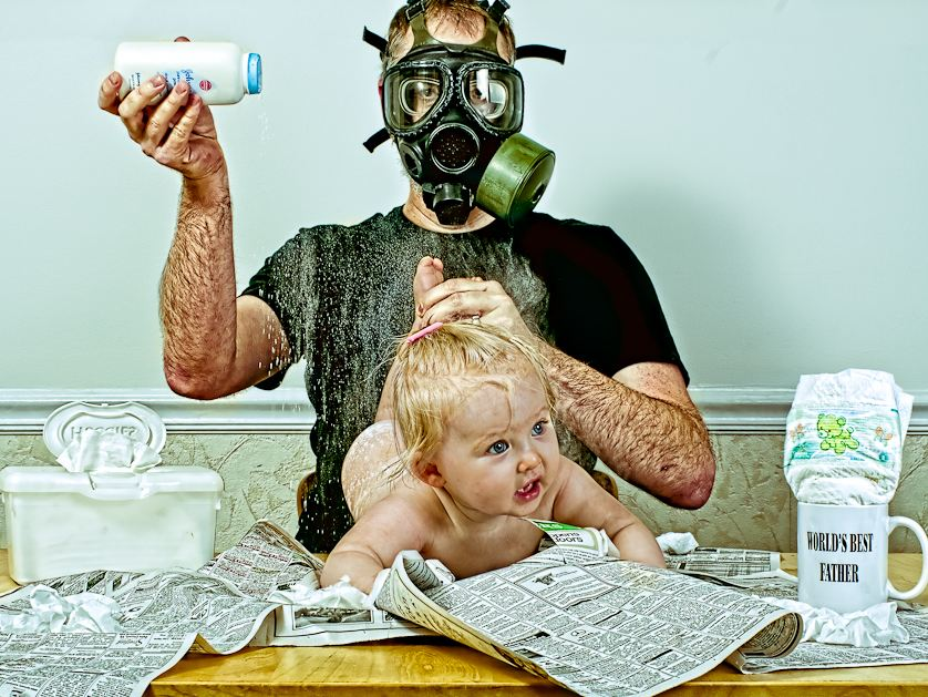 Dad wearing gas mask while changing diaper