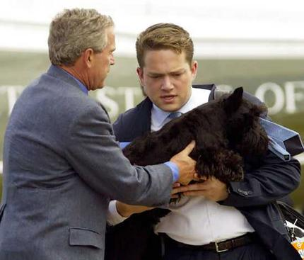 George Bush hands his Scottish terrier Barney to his personal aide, Blake Gottesman, as he prepares to board Air Force One. Photo: AFP