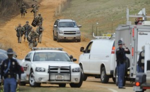 Mickey Welsh/AP -  Heavily armed officers near the suspect's home at the scene of a Dale County hostage crisis in Midland City, Ala., on Jan. 30.