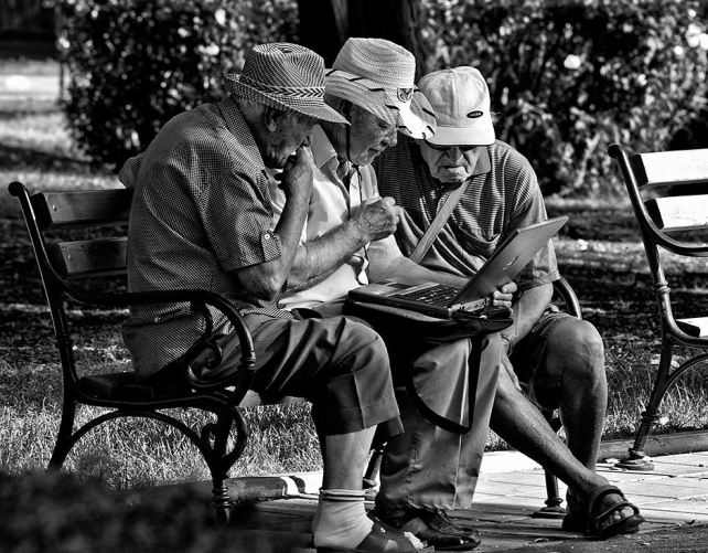Three elderly men surfing the web while in the park