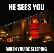 Large Santa ornament peering in 2nd floor window of a home.