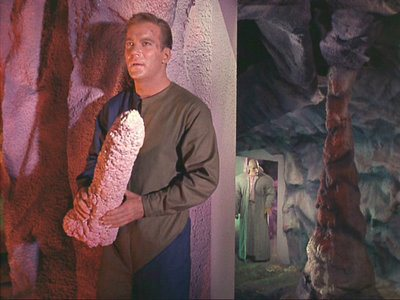 A behind-the-scenes photo of Captain Kirk holding a rather phallic stalactite.
