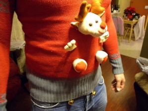 A stuffed reindeer looks like it's coming out of the man's belly.