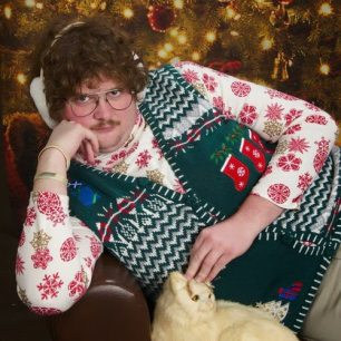 Ugly Christmas sweater holiday photo posing with cat.